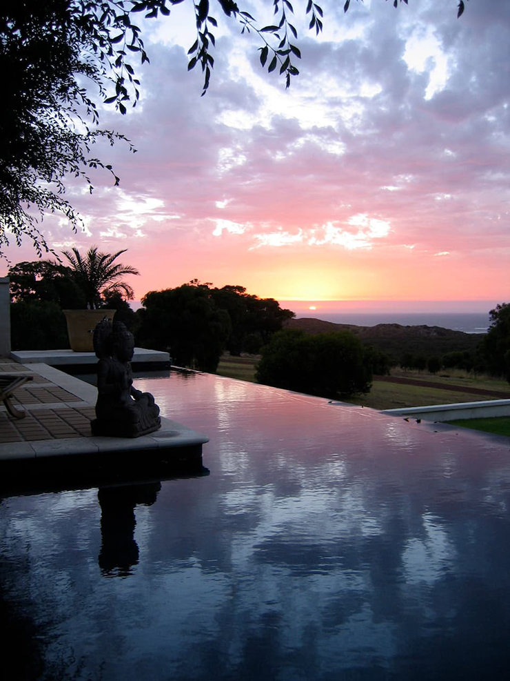 An infinity pool drenched in crimson tones from the evening sun.