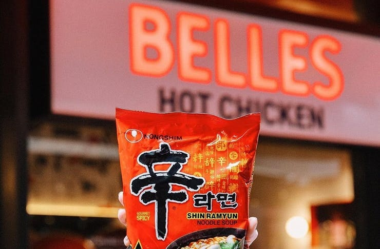 A packet of Shin Ramyun noodles held up against the Belles Hot Chicken neon sign.