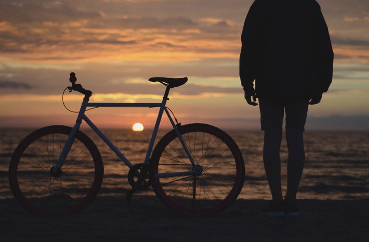 A man standing beside his bike at the seaside at sunrise.