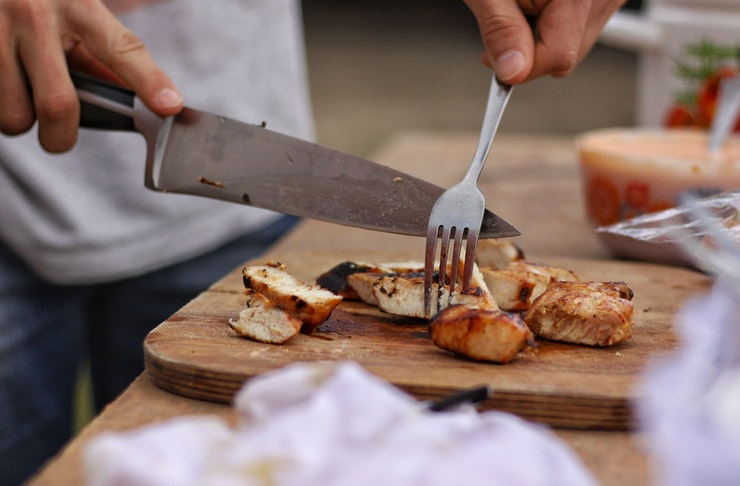 A person cutting chicken on a wooden chopping board using a chef's knife.