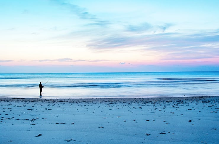 Perth beach at sunset with a person fishing.