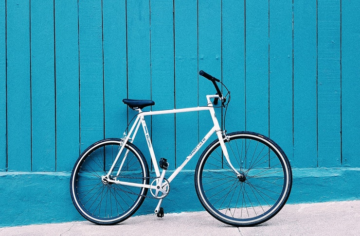 A white cycle leans up again a turquoise-coloured wall.