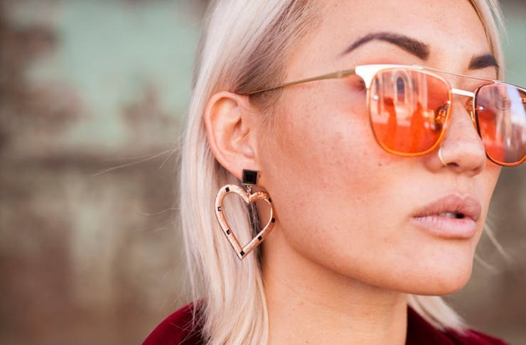 A blonde-haired woman with killer eyebrows wears rose-tinted sunglasses.