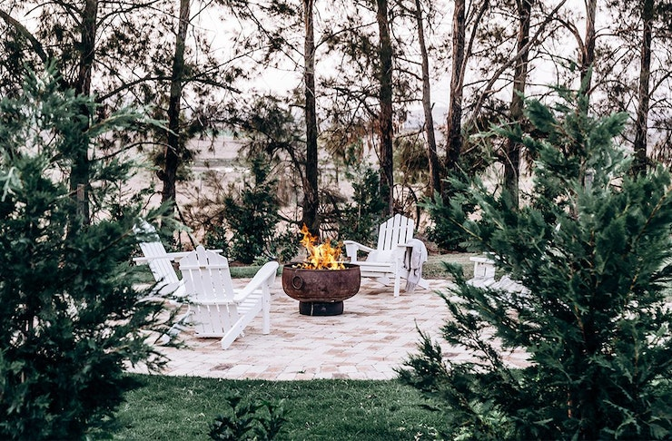 An outdoor fireplace with white deckchairs around it.