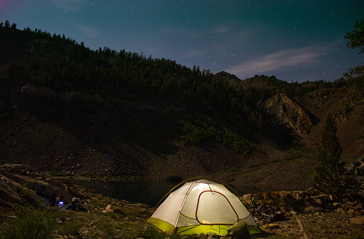 Light shining through a tent in the wilderness at night.