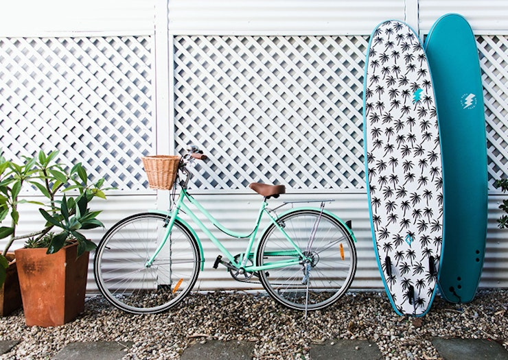 Two surfboards and a turquoise cruise bike lean up against a white wall.