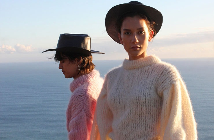 Two models wearing Frisson Knits chunky knit sweaters. One in cream and one in soft baby pink.