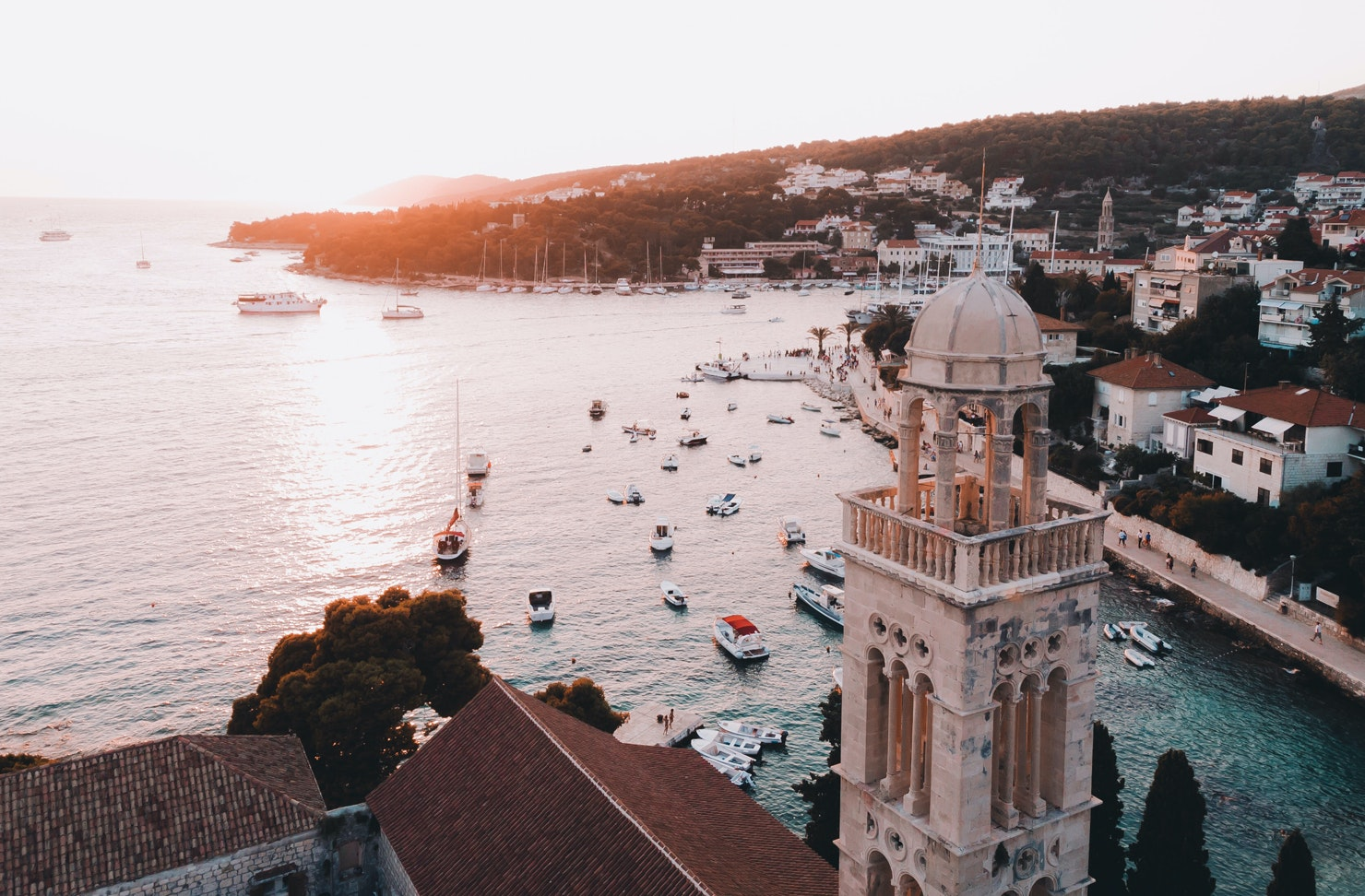 Overlooking a town on Hvar in Croatia, with buildings in the foreground and sailing boats moored in the sea.