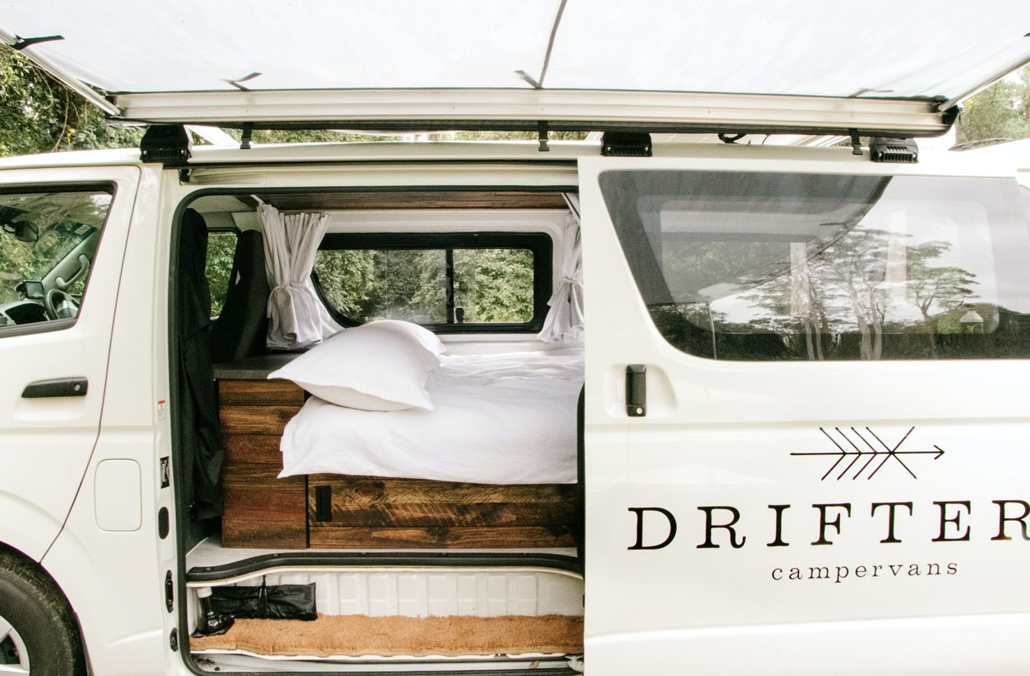 A white camper van with a mattress inside.