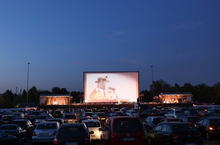 Cars parked in front of cinema screen.