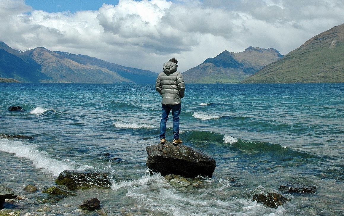 A man stands out looking at beautiful NZ scenery wearing a jacket from Edmund Hillary, a brand at Commercial Bay's new shopping district.