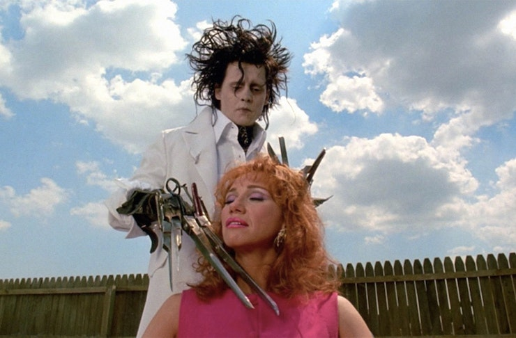 Johnny Depp as Edward Scissorhands gives a lady a hair cut in the garden.