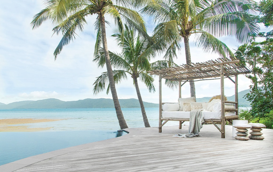 A day bed sitting on a deck next to the pool overlooking the ocean at Elysian Retreat