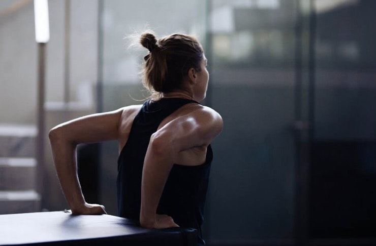 Woman in black exercise gear has back facing a table she is using to support herself doing a squat