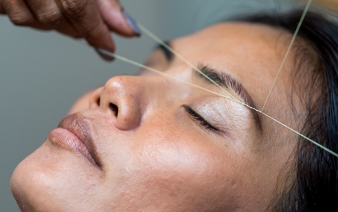 A woman reclines as someone gives her eyebrows a good threading.