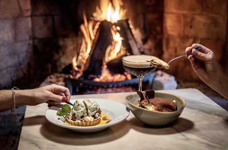 A couple dig into some delicious looking fare by the fireplace at Fenice restaurant on Waiheke Island.