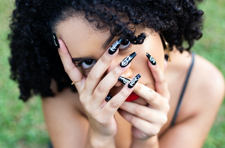 Woman covering her face with her hands, Best Places To Get Your Nails Done in Auckland