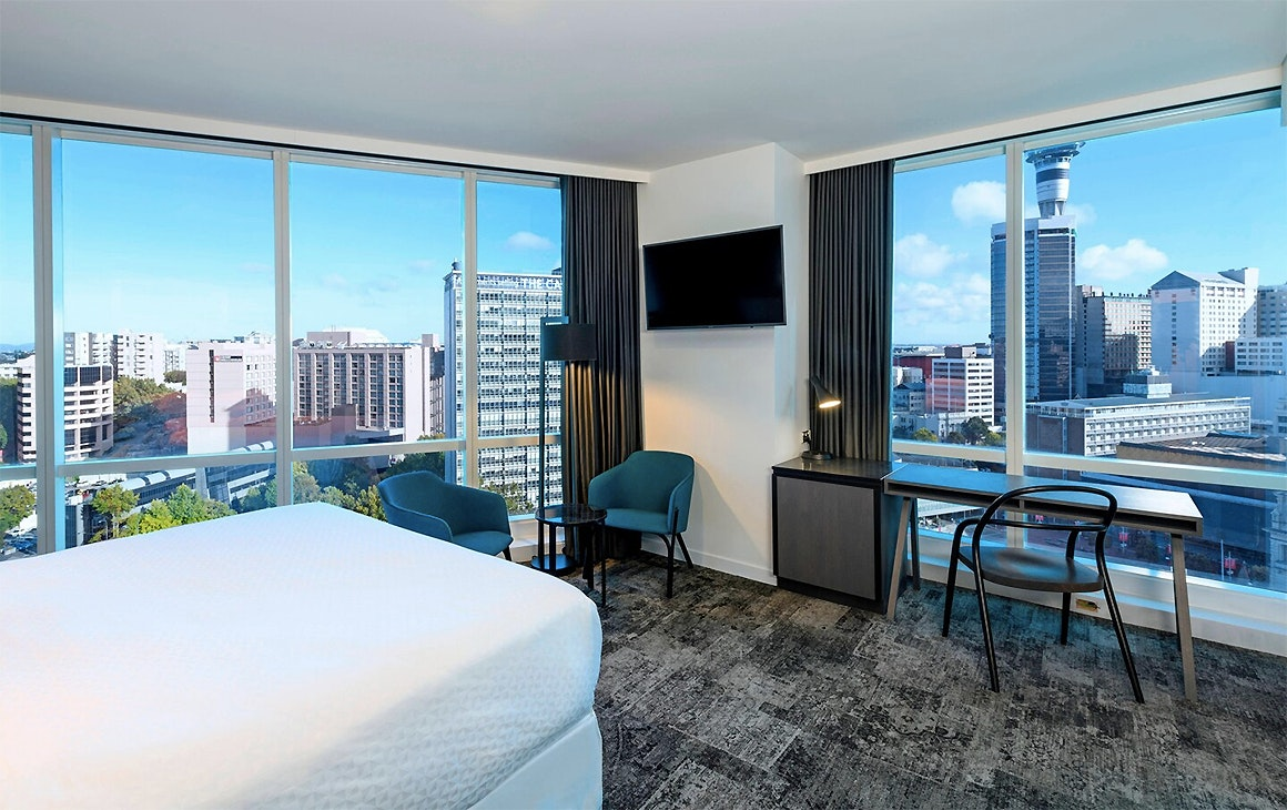 A corner room at the Four Points By Sheraton showing the Sky Tower in the distance and plush furnishings.