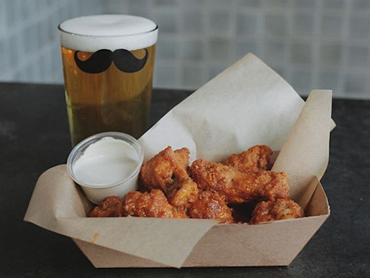 A box of wings and a beer glass with a moustache on it