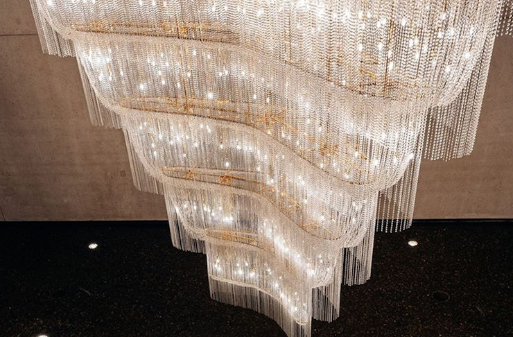 A large triangular shaped chandelier on display at QAG.