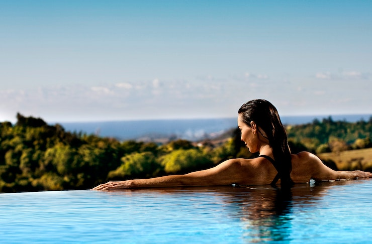 A woman looks over the edge of an infinity pool towards the Gold Coast, at Gwinganna Lifestyle Retreat.
