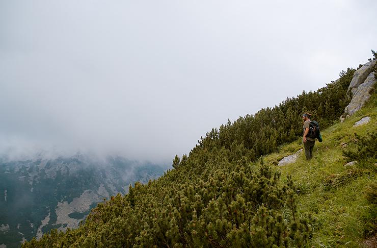 A man hiking along a mountain on a misty morning.