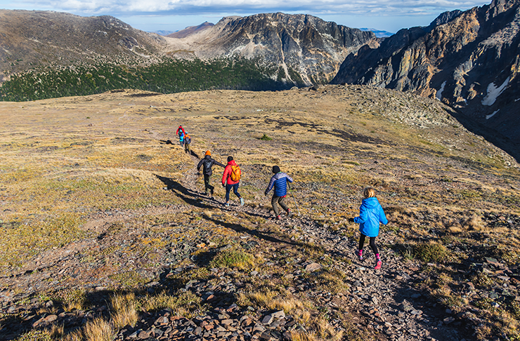 Three people hiking through a field towards several snow-capped mountains.