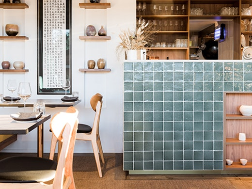A shot of a restaurant interior with a turquoise ceramic counter and decorative ceramic accents.