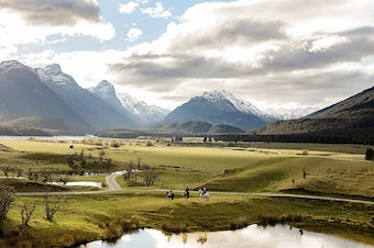 Three people sit on horseback in  stunning Glenorchy