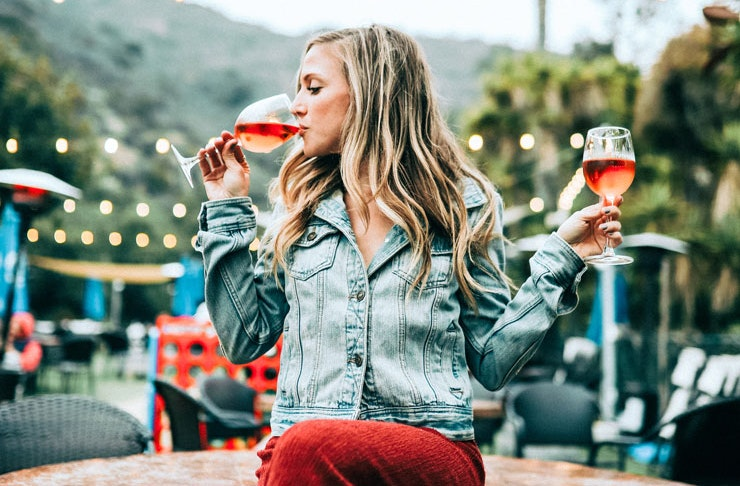 A woman sitting on a table holding two glasses of rose wine.