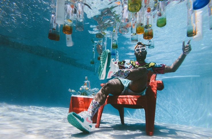 A man underwater n a pool with a red esky and drinks suspended around him.