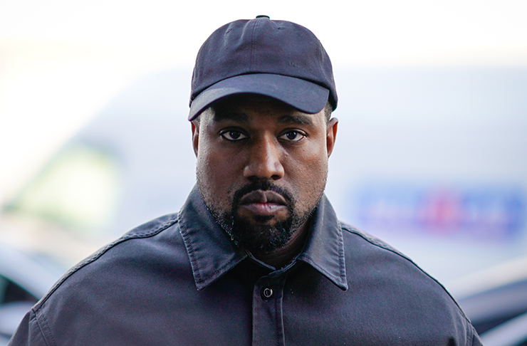 Kanye West looking directly into the camera, wearing a black button-up shirt.