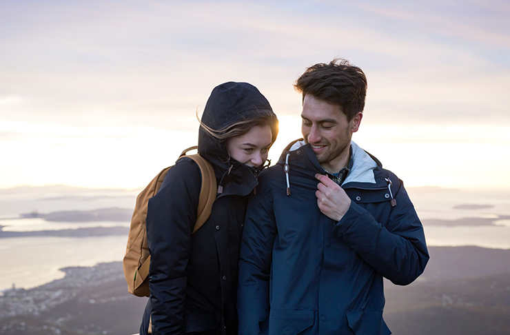 Two hikers standing on the top of a peak smiling and wearing rain jackets.