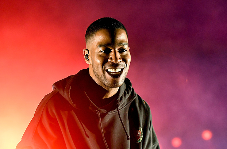 Rapper Kid Cudi smiling in a large hooded sweater.