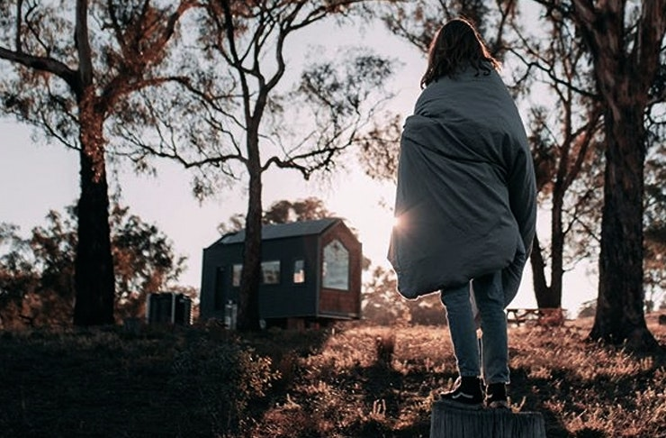 A woman rugged up in a blanket looking at a tiny home perched amidst the gumtrees.