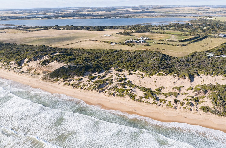 a retreat on a stunning coastline, viewed from a drone above the ocean