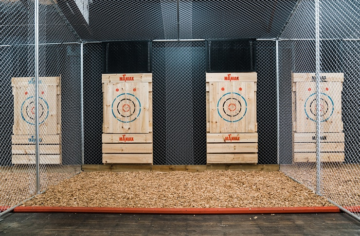 A row of axe throwing targets lined up in a cage.
