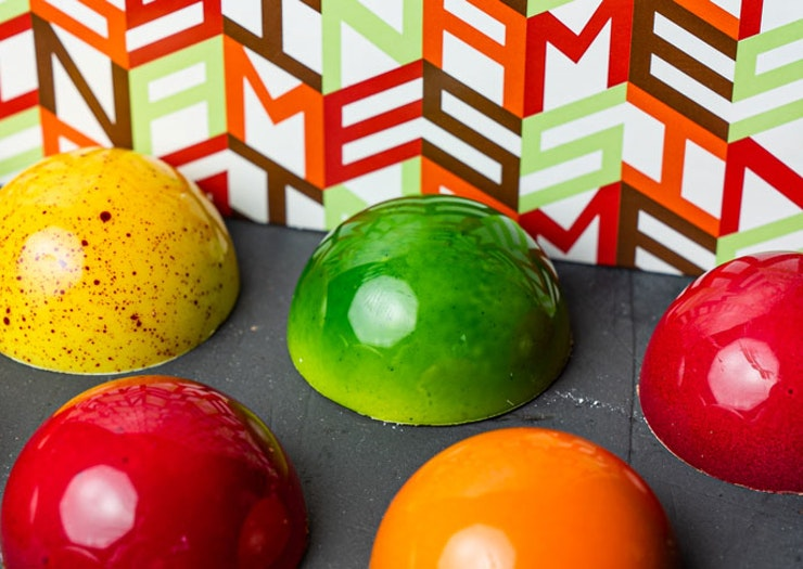 Gelato Messina's new chocolate bon bons, which look like half spheres in fruit salad colours like apple red and green, orange and banana yellow.