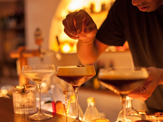 A bartender sprinkles coffee beans on a row of espresso martinis.