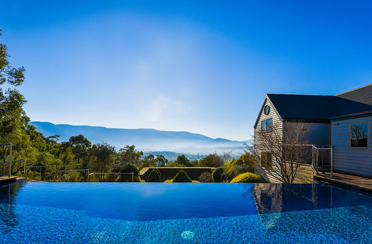 A pool overlooking mountains on a misty morning.