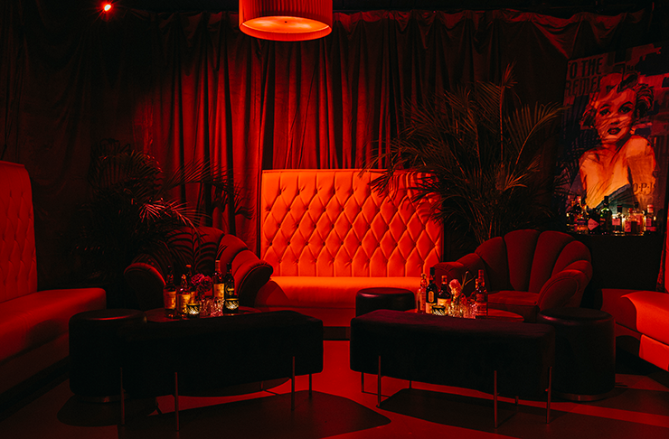 Mr Brownie's underground bar featuring two red velvet couches backed by red velvet curtains.