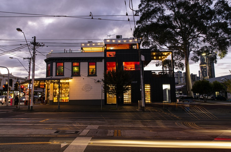 The four-story pub, Mr Brownie, lit up with neon and interior lights against a cloudy horizon in the evening.