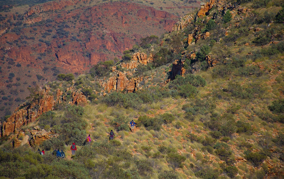a line of people hiking up a grass covered hillside