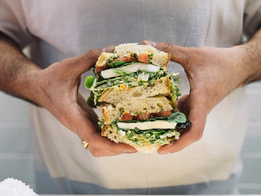 A stacked deli sandwhich being held in two hands from Nico's Sandwich Deli.