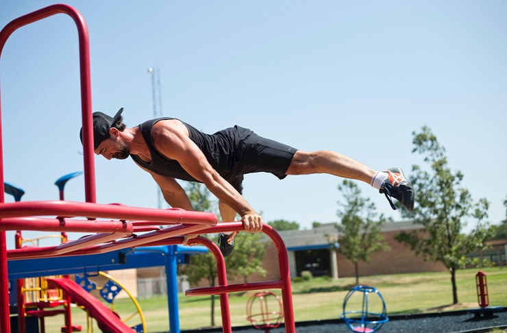 A man holding himself up vertically on a set of monkey bars.