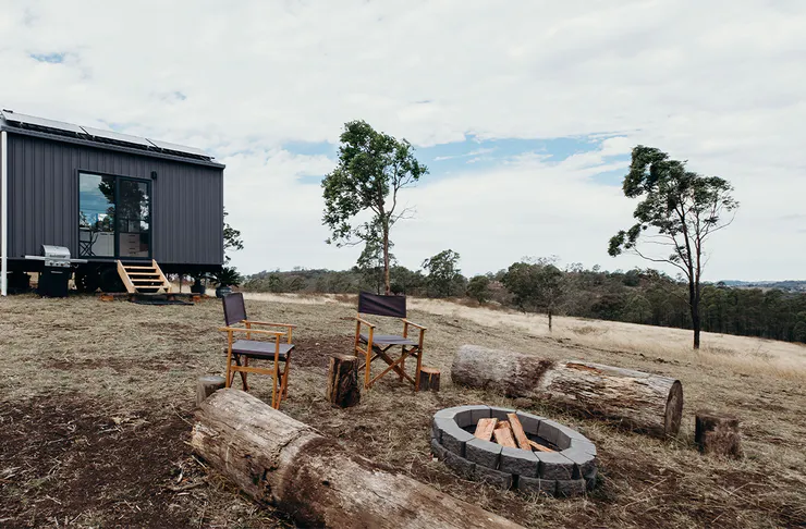 A tiny home at the top of a rolling hillside with a firepit in front of it.