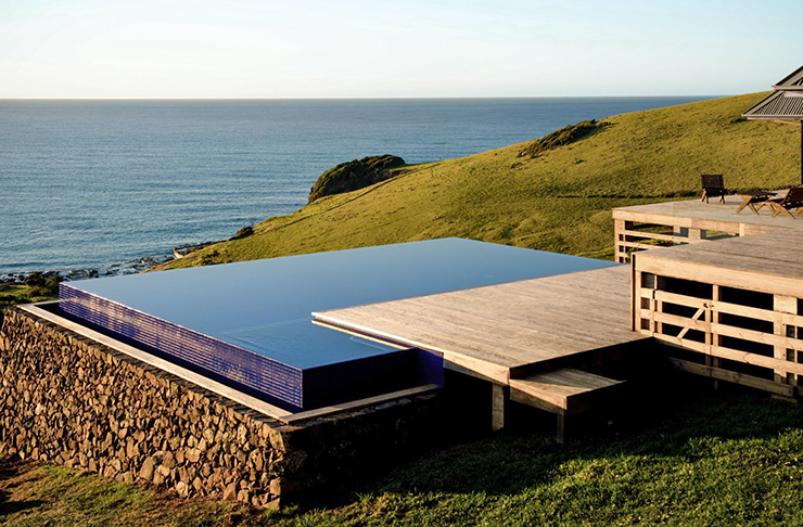 A square infinity pool on a grass hill overlooking the ocean.