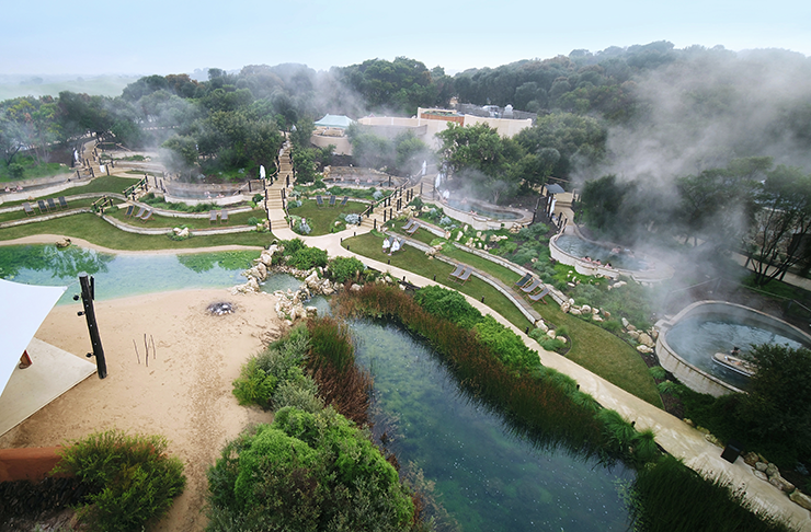 The main grounds of the just-reopened Peninsular Hot Springs. Steam rising from the pools between patches of lush green grass.