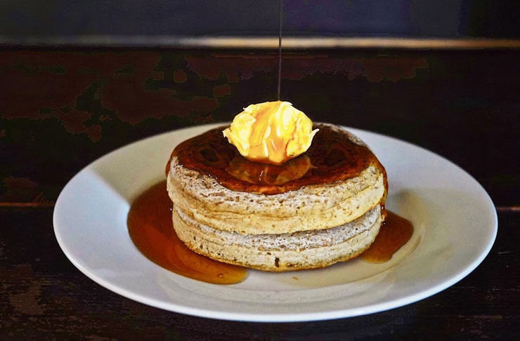 A white plate with two chocolate crumpets, drizzled with maple butter and topped with salted butter.