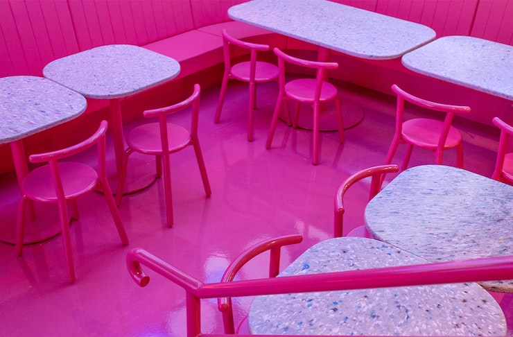 a restaurant interior with pink floors and chairs